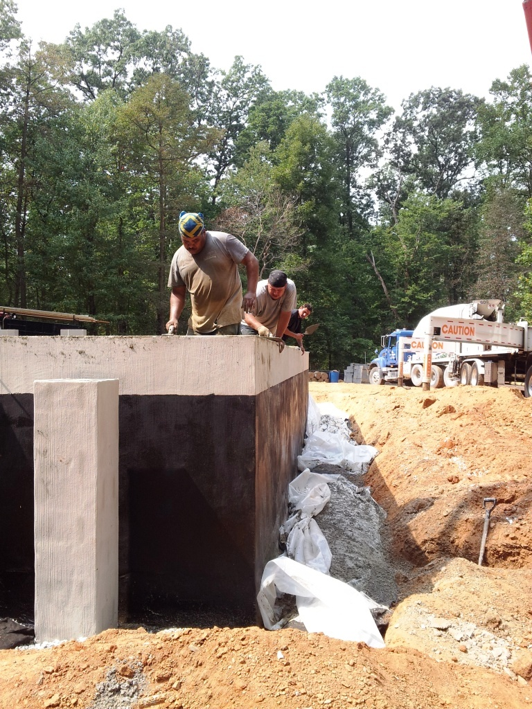 Passive House masonry crew sets anchor bolts in wet concrete