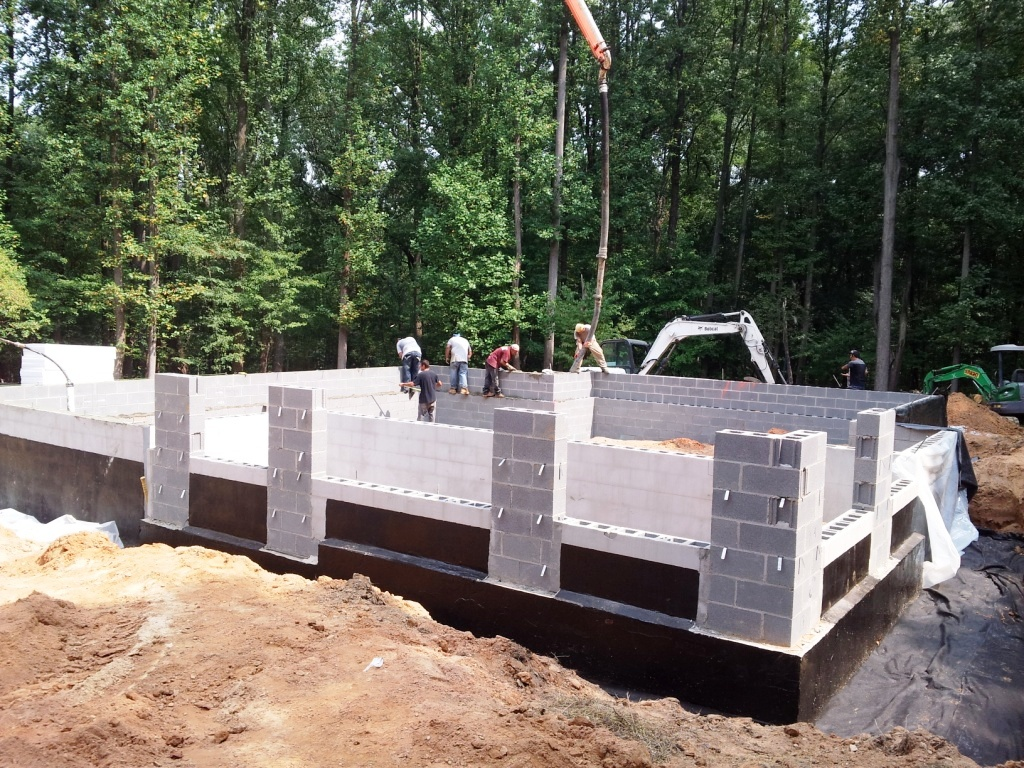 Passive house masonry crew reinforces foundation walls